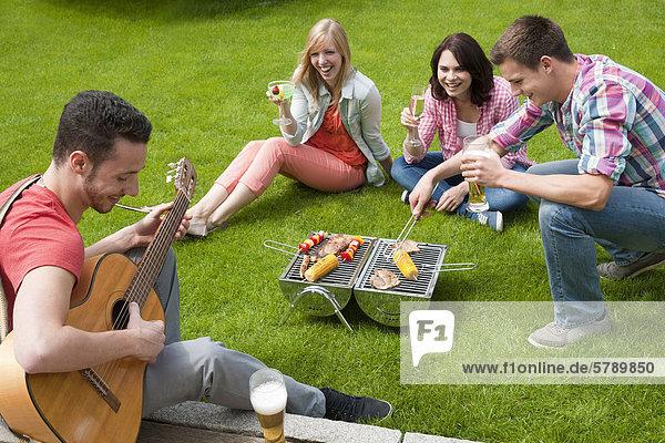 Freunde grillen auf dem Rasen