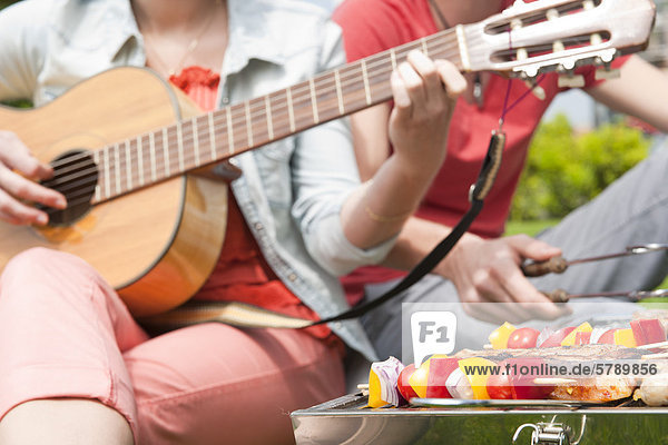 Couple barbecueing and playing guitar