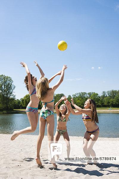 Vier Mädchen in Bikinis spielen mit einem Ball an einem Badesee