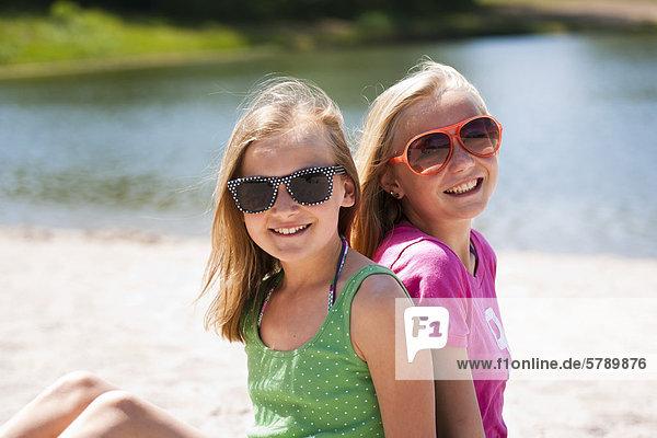 Lächelnde Mädchen mit Sonnenbrillen sitzen an einem Badesee