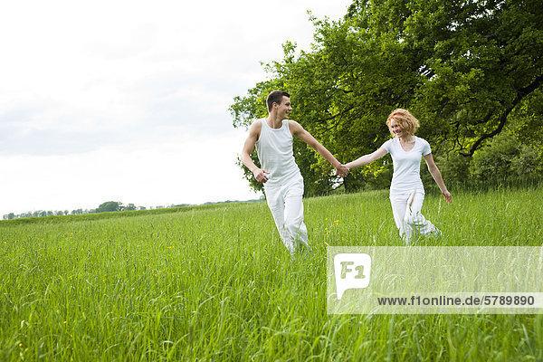 Junges Paar rennt auf einer Wiese