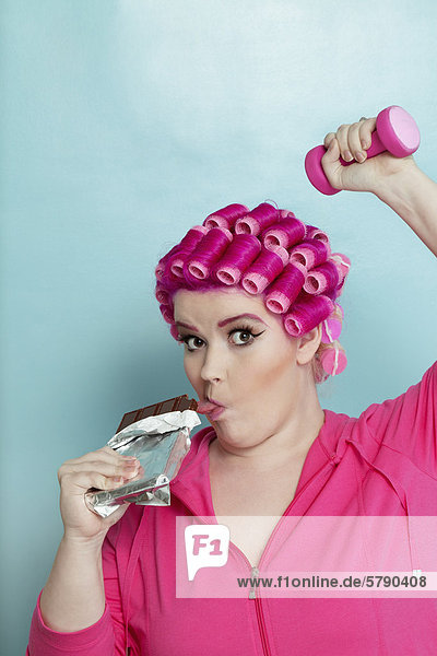 Portrait of young woman licking chocolate bar while light dumbbell over colored background