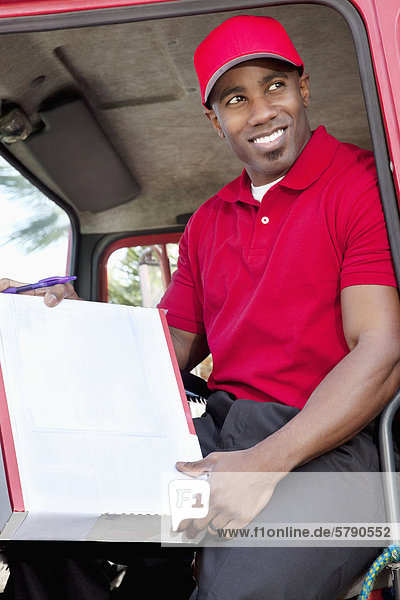 Young African American man sitting in delivery truck with box