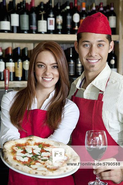 Porträt eines jungen warten Personal mit Glas Wein und pizza