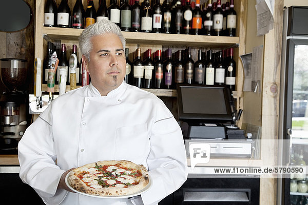 Mid adult chef holding pizza while looking away