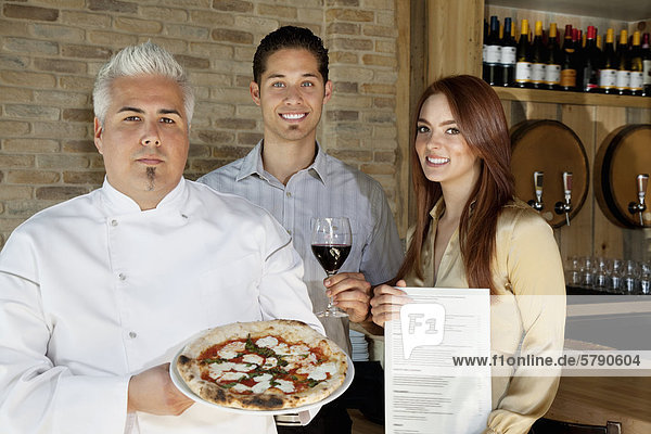 Porträt von glückliches junges Paar mit Küchenchef hält pizza