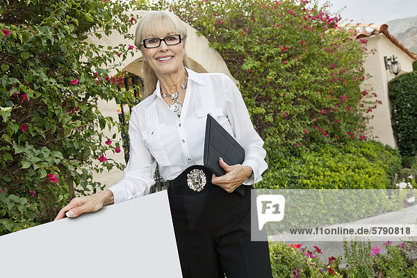 Portrait of a happy senior woman standing by sign board with clipboard