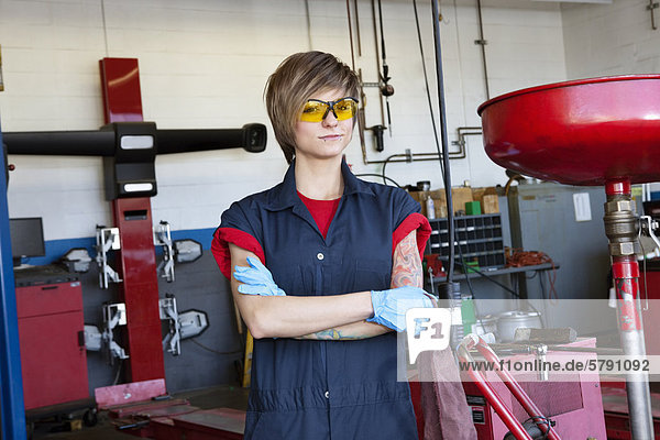 Portrait of a young female mechanic wearing protective gear with arms crossed in workshop