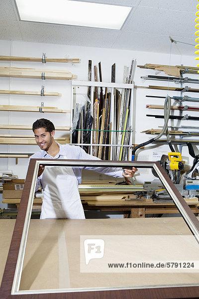 Porträt von glücklich Handwerker arbeiten an Bilderrahmen in Werkstatt