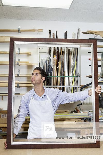 Junge Handwerker suchen auf Ecke des Rahmens in der Werkstatt