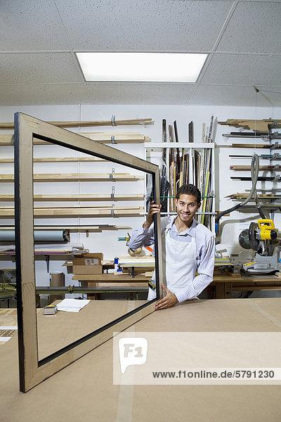 Porträt von glücklich junger Mann arbeitet an großen Bilderrahmen in Werkstatt