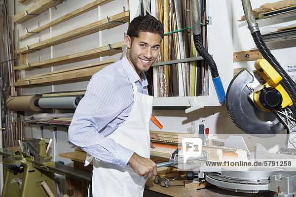Porträt der glückliche junge Handwerker stehend von Kreissäge-Maschinen