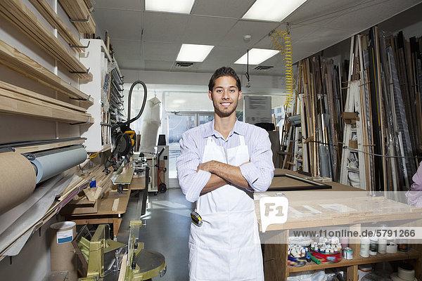 Porträt der glückliche junge Handwerker stehend mit Arme verschränkt in Werkstatt