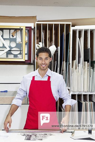 Porträt der glückliche junge Facharbeiter stehend mit Meter Stock in der Werkstatt