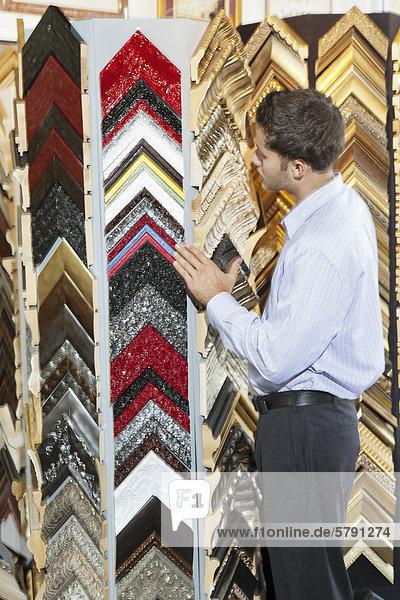 Junger Mann in einem Frame Store durchsuchen