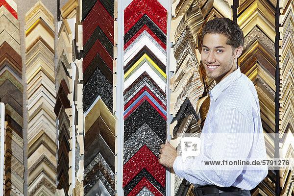Porträt eines glücklichen jungen Mannes mit Multi farbige Bilder im Hintergrund