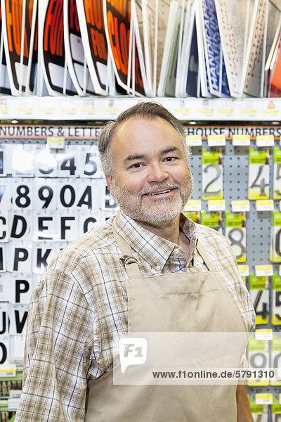 Portrait of a happy mature salesperson in hardware store