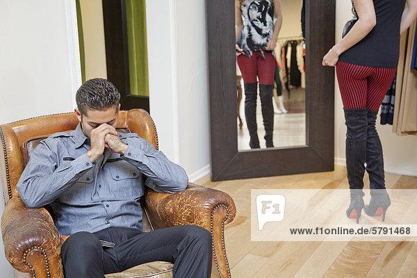 Müde junger Mann sitzt auf Sessel mit Frau im Hintergrund