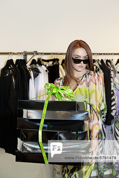 Portrait of a young woman wearing sunglasses carrying boxes in fashion clothing store