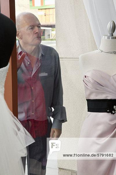 Senior man looking at wedding dress displayed on window in bridal store