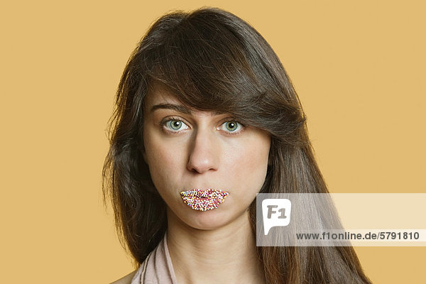 Portrait of a beautiful young woman with sprinkled lips over colored background