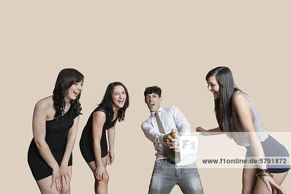 Junge Freunde öffnen Champagnerflasche über farbigen Hintergrund