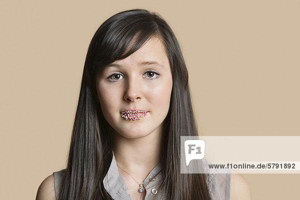 Porträt einer schönen jungen Frau mit bestreut Lippen über farbigen Hintergrund