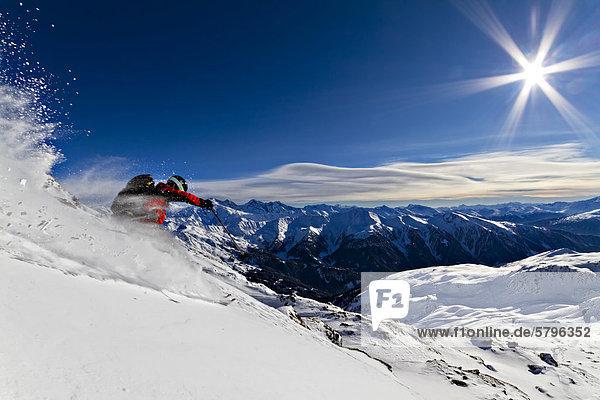 Skifahrer im Pulverschnee mit Sonnenschein  Tuxer Alpen  Tirol  Österreich  Europa