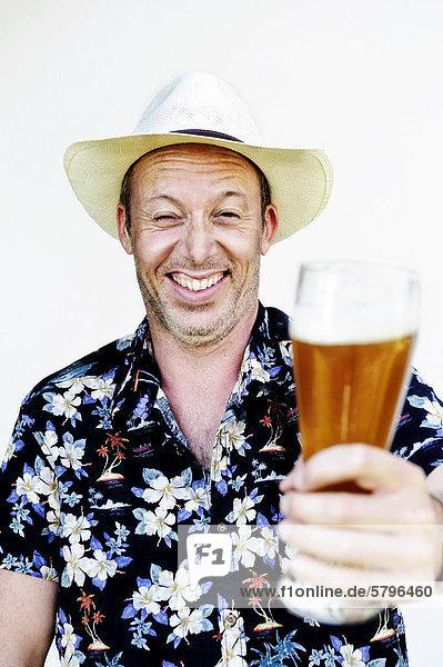 Lachender Mann mit Strohhut und Hawaiihemd hält ein Weizenbier in der Hand Lachender Mann mit Strohhut und Hawaiihemd hält ein Weizenbier in der Hand