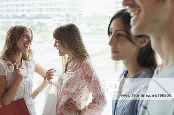 Junge Frauen beim Plaudern  vorbeikommende Menschen im Vordergrund