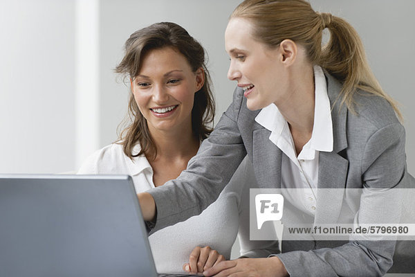 Weibliche Kollegen  die gemeinsam am Laptop arbeiten