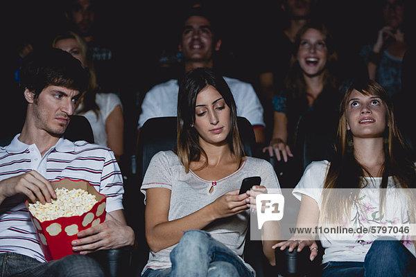 Frau mit Handy im Kino  Mann schaut mit verärgertem Gesichtsausdruck rüber