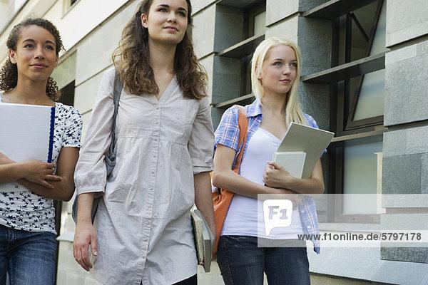 Studentinnen  die im Freien spazieren gehen.