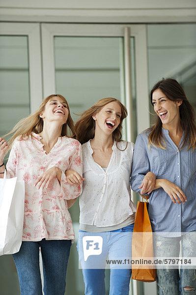 Junge Frauen gehen zusammen und tragen Einkaufstaschen.