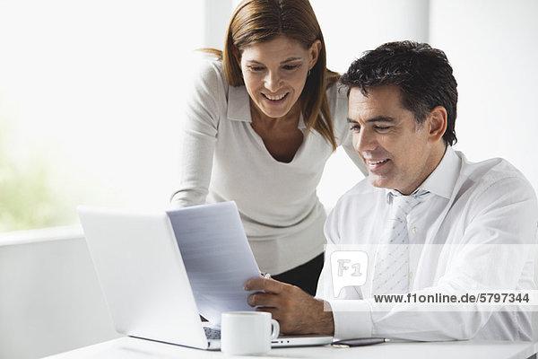 Geschäftskollegen  die gemeinsam auf den Laptop schauen