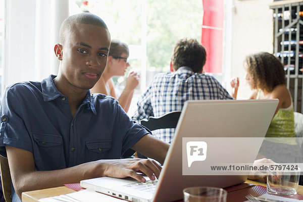 Young man using laptop computer in cafe