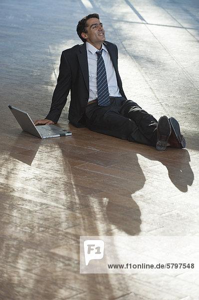 Geschäftsmann beim Ausruhen im Freien mit dem Laptop Geschäftsmann beim Ausruhen im Freien mit dem Laptop