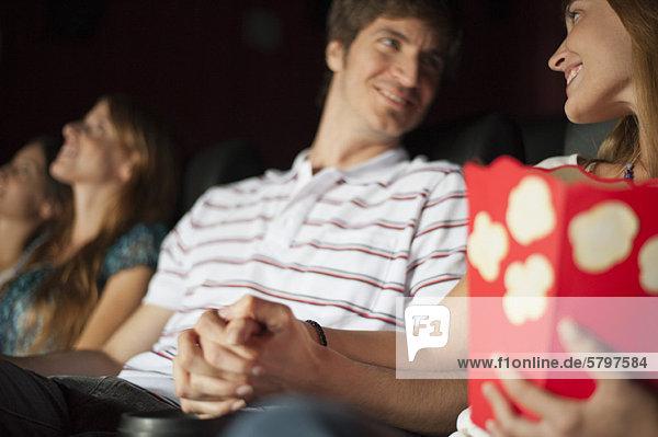 Ein Paar schaut sich an und hält sich an den Händen im Kino.