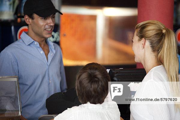 Mutter und Sohn bestellen Essen am Tresen  Rückansicht