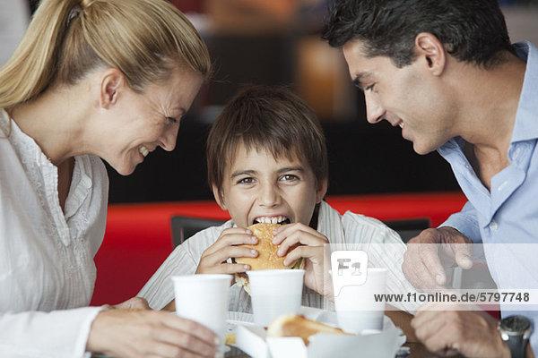 Junge isst Hamburger mit seinen Eltern im Fast-Food-Restaurant