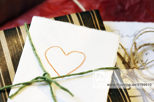 Close-up of heart drawn on paper tied with gift