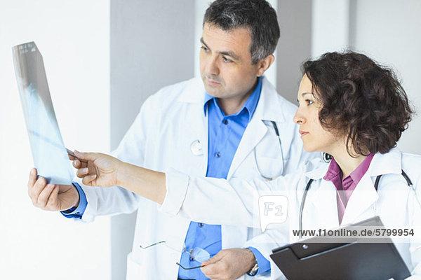 Ärztin zeigt auf medizinischen Röntgen-Testbericht  während der Chirurg im Krankenhaus nachsieht.