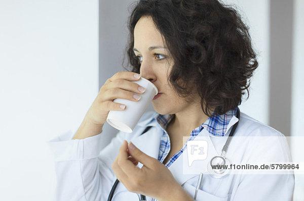 Junger Arzt beim Kaffeetrinken in der Pause im Krankenhaus