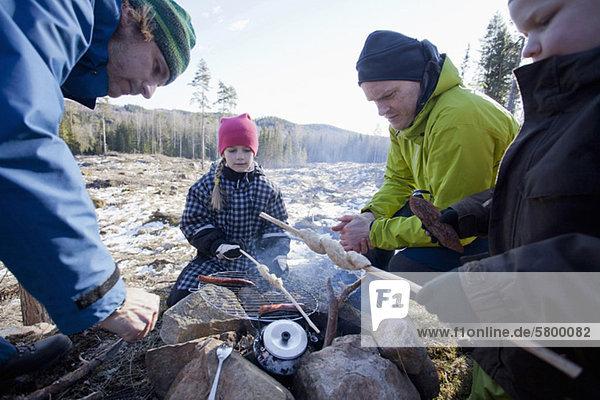 Männer kochen  während Kinder auf den Campingplatz schauen