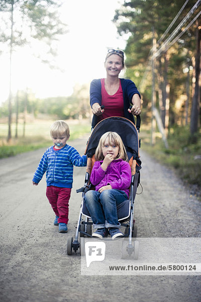 Mother with two children pushing baby carriage on country road