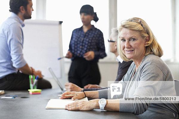 Porträt einer älteren Frau lächelnd mit Kollegin im Hintergrund