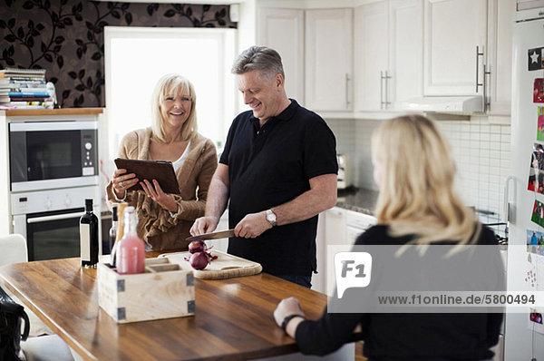 Lächelndes Paar in der Küche mit digitaler Tablette für Rezept und Kochmahlzeit
