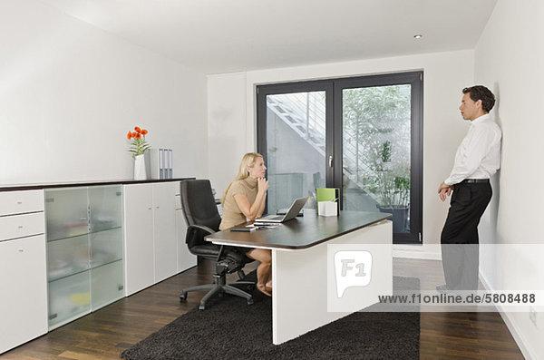 Ernster Geschäftsmann und Geschäftsfrau im Büro
