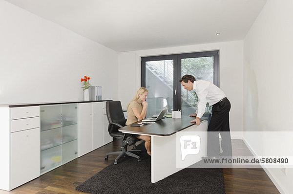Geschäftsmann lächelt Geschäftsfrau am Schreibtisch an