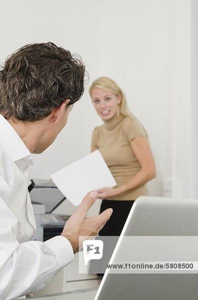Geschäftsmann spricht mit Frau am Kopierer